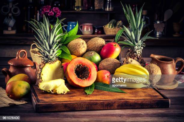 assorted tropical fruits on cutting board in a rustic kitchen. natural lighting - papaya stock photos and pictures