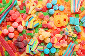 Assorted variety of sour candies includes extreme sour soft fruit chews, keys, tart candy belts and straws. Flat lay, sugar background concept for kids birthday party.