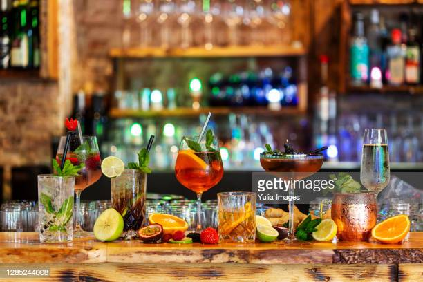 assortment of alcoholic cocktails on a bar counter - cocktail party foto e immagini stock