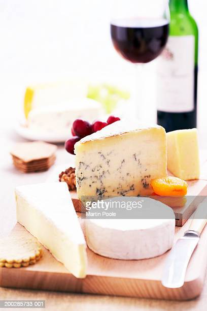 Assortment of cheeses and knife on wooden cheese board, close-up, glass and bottle of red wine in background