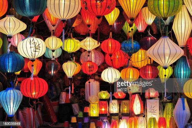Assortment of colorful Asian lanterns lit up in a dark room