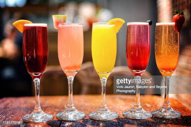 assortment of colorful brunch cocktails, including mimosas and other fruit concoctions - mimosa stockfoto's en -beelden