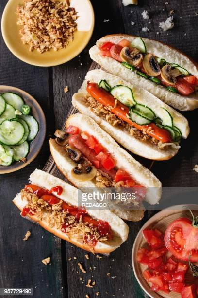 Assortment of homemade hot dogs with sausage fried onion tomatoes and cucumber served with ingredients in different plates on wood chopping board...