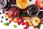 assortment of jams, seasonal berries, plums, mint and fruits