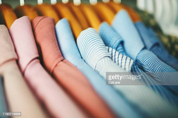 assortment of mens shirts on wooden coat hangers - rack stock pictures, royalty-free photos & images