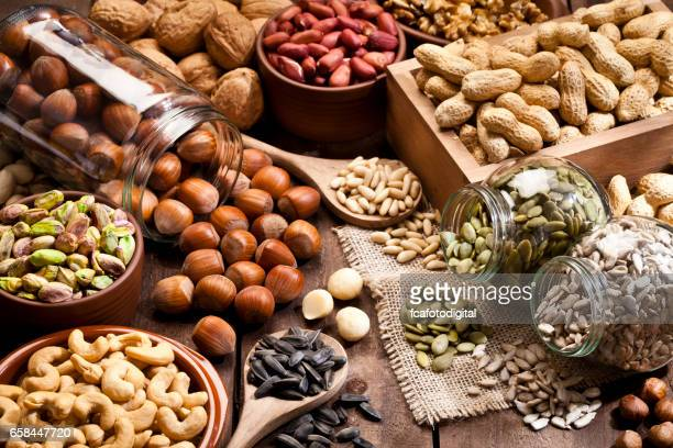 assortment of nuts on rustic wood table. - nut food stock pictures, royalty-free photos & images