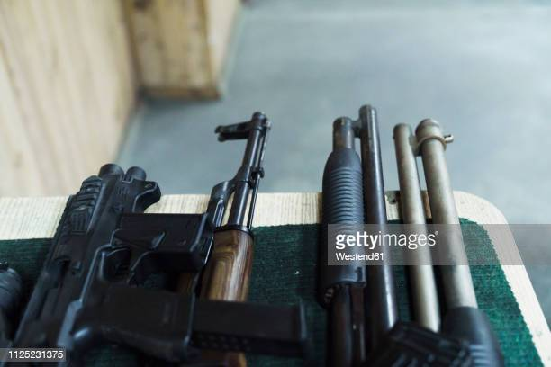 assortment of rifles on table in an indoor shooting range - gun barrel stock pictures, royalty-free photos & images