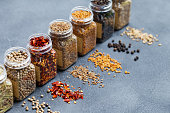 Assortments of spices, white pepper, chili flakes, lemongrass, coriander and cumin seeds in jars on grey stone background. Copy space.