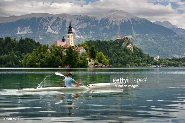 Assumption of Mary pilgrimage church Beld Island and kayaker on Lake Bled with Bled castle on cliff and Sol massive of Karavanke mountains Slovenia