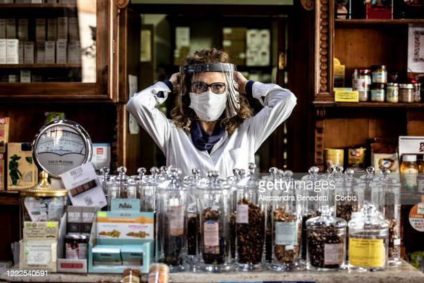 Assunta owner of the herbalist's shop Il Germoglio is portrayed while adjusting her protective gear against Covid-19 on May 2, 2020 in Rome, Italy....