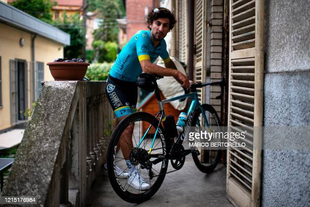 Astana cycling team Italian rider Fabio Felline poses with his bicycle at home on May 19 in Turin, Piedmont, as the country eases its lockdown aimed...