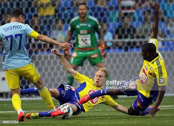 Astana midfielder Dmitri Shomko vies with HJK Helsinki defender Valtteri Moren and midfielder Guy Moussi during the second leg football match between...