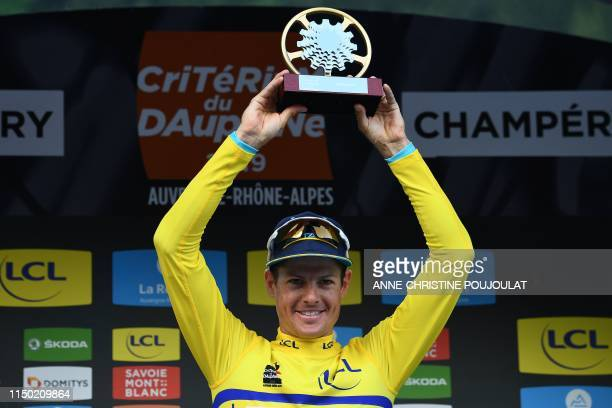 Astana Pro Team rider Denmark's Jakob Fuglsang holds up his trophy as he celebrates his overall leader's yellow jersey on the podium of the eighth...