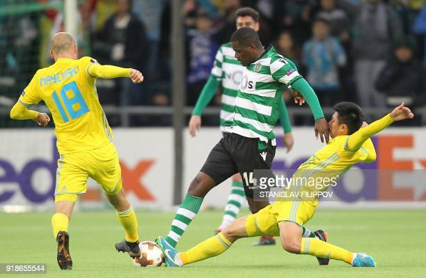 Astana's Belarussian midfielder Ivan Maevski and Astana's midfielder Abzal Beysebekov tackle Sporting's midfielder William Carvalho during the Europa...