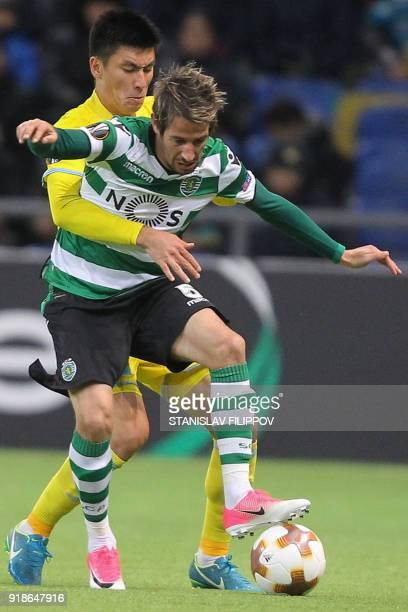 Astana's defender Abzal Beisebekov vies with Sporting's defender Fabio Coentrao during the Europa League Round of 32 first leg football match between...