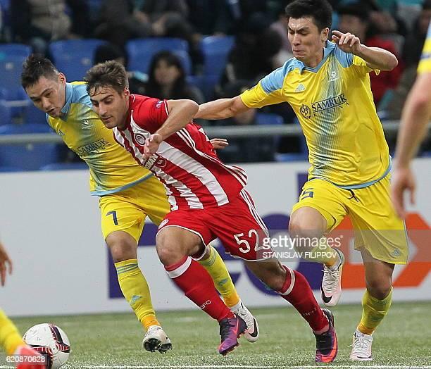 FC Astana's Kazakh midfielder Serikzhan Muzhikov and FC Astana's Kazakh defender Abzal Beysebekov vie for the ball with Olympiacos' Giorgos Manthatis...