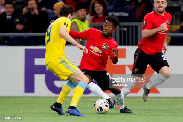 Astana's Romanian midfielder Dorin Rotariu and Manchester United's midfielder Angel Gomes vie for the ball during the UEFA Europa League group L...