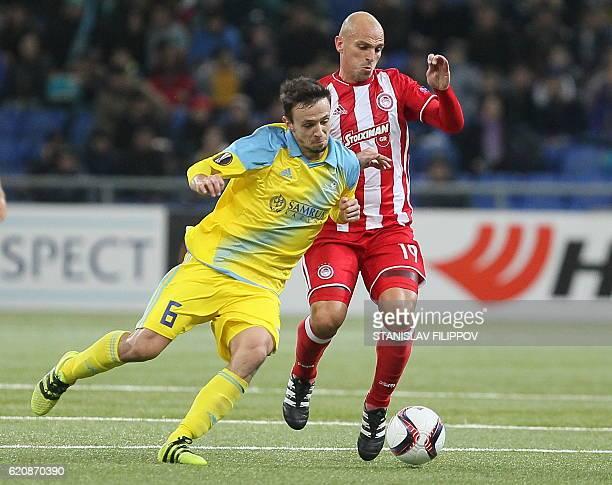 FC Astana's Serbian midfielder Nemanja Maksimovic and Olympiacos' Esteban Cambiasso vie for the ball during the UEFA Europa League group B football...
