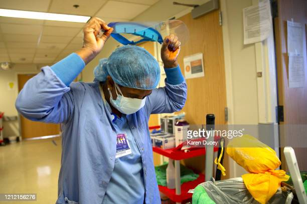 Aster Mekonen with housecleaning services takes off her PPE after cleaning and disinfecting a room that had a patient with COVID19 in it in the acute...