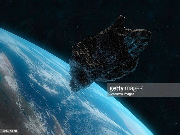 asteroid in front of the earth. - asteroid stock pictures, royalty-free photos & images