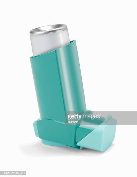 Asthma inhaler, against white background, close-up