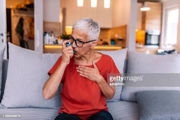 asthmatic woman using an inhaler - bomba para asma imagens e fotografias de stock
