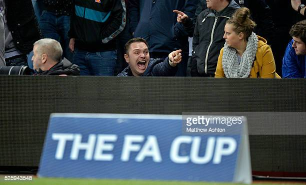 Aston Villa fan points and laughs at the travelling West Bromwich Albion Fans behind an FA Cup advertising hoarding