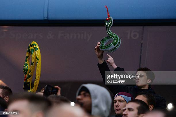 Aston Villa fans hold up inflatable snakes as former Aston Villa player and now Manchester City's English midfielder Fabian Delph takes to the pitch...