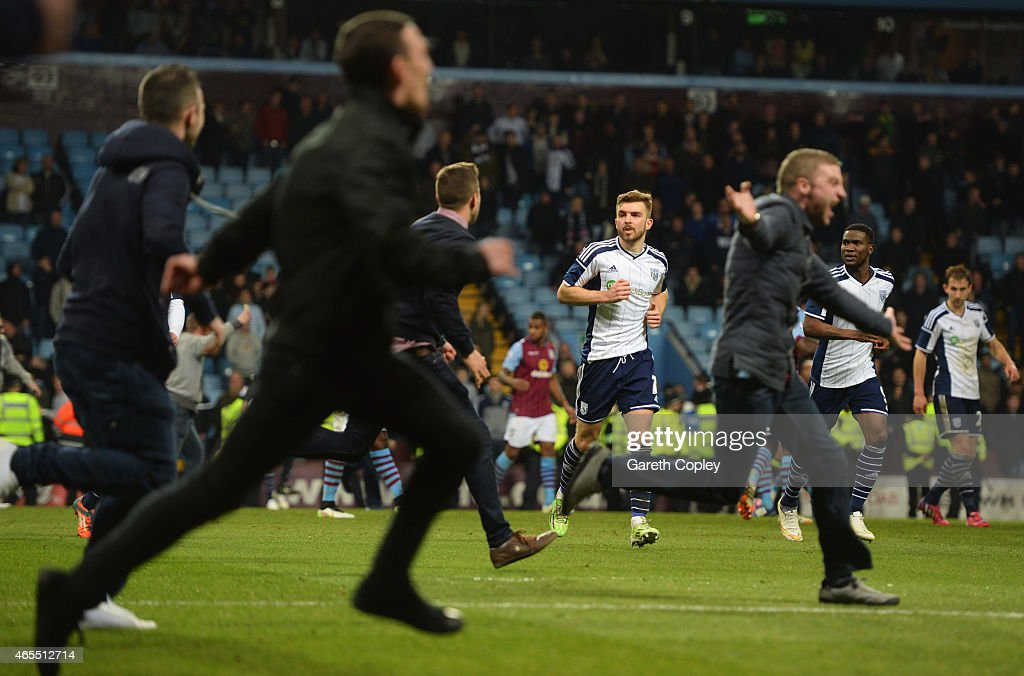Aston Villa fans invade the pitch in celebration as James Morrison of West Bromwich Albion (C) and team mates look on after the FA Cup Quarter Final match between Aston Villa and West Bromwich Albion at Villa Park on March 7, 2015 in Birmingham, England.