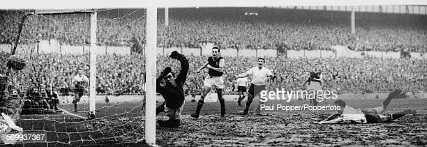 Aston Villa goalkeeper Nigel Sims dives for the ball as Tottenham Hotspur football player Cliff Jones scores a goal watched by Spurs player Bobby...