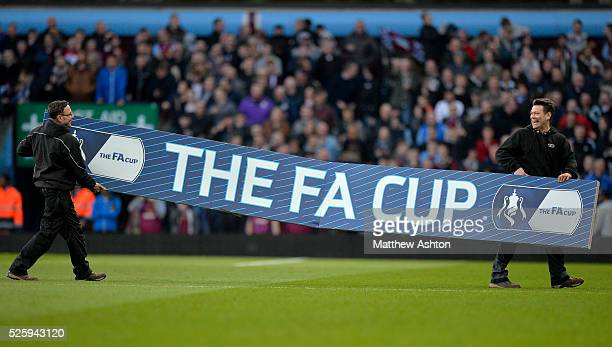 Aston Villa ground staff carry a huge FA Cup advertising / branding hoarding across the pitch moments before the kickoff