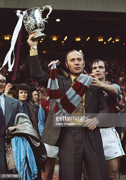 Aston Villa manager Ron Saunders holds the trophy aloft as captain Ian Ross drapes a Villa scarf around his neck after the 1975 League Cup Final...