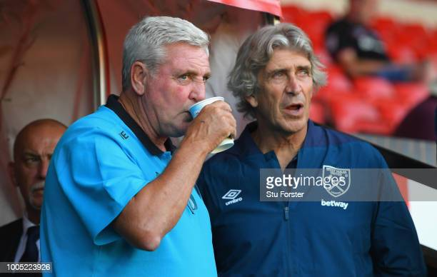 Aston Villa manager Steve Bruce with West Ham manager Manuel Pellegrini during a friendly match between Aston Villa and West Ham United at Banks'...