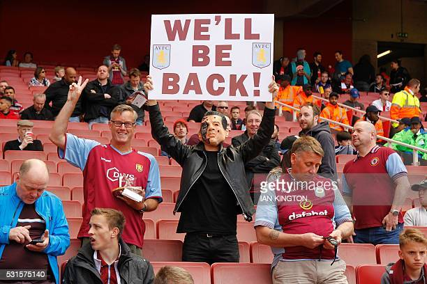 Aston Villa supporter holds a placard that reads 'We'll be Back' ahead of the English Premier League football match between Arsenal and Aston Villa...