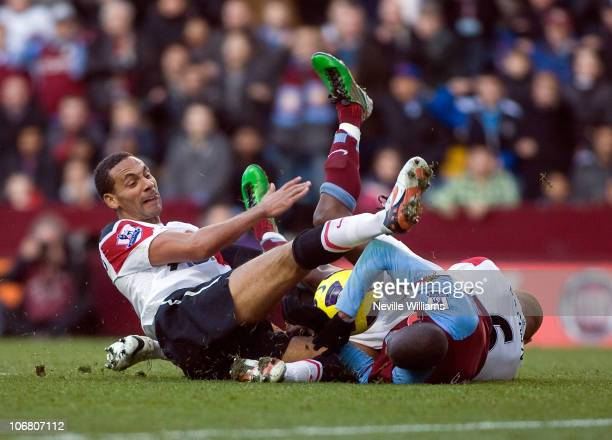 Aston Villa's Ashley Young is fouled by Manchester United's Wes Brown and Rio Ferdinand for Aston Villa's penalty during the Barclays Premier League...
