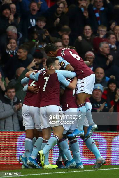Aston Villa's Egyptian midfielder Trezeguet celebrates with teammates after he scores his team's first goal during the English Premier League...