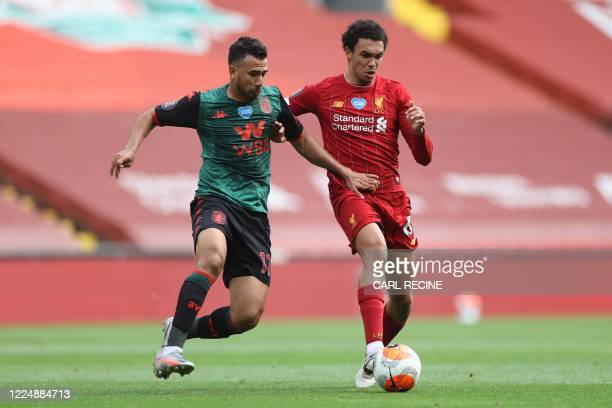 Aston Villa's Egyptian midfielder Trezeguet challenges Liverpool's English defender Trent Alexander-Arnold during the English Premier League football...
