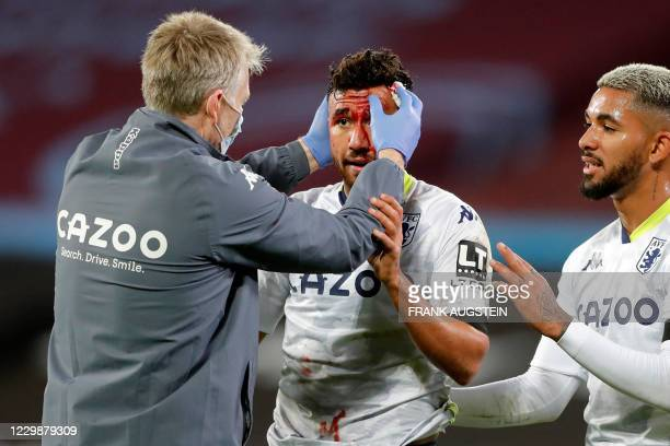 Aston Villa's Egyptian midfielder Trezeguet is treated after picking up a facial injury during the English Premier League football match between West...