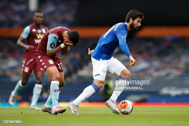 Aston Villa's Egyptian midfielder Trezeguet vies with Everton's Portuguese midfielder André Gomes during the English Premier League football match...