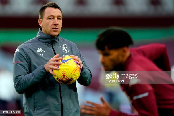 Aston Villa's English assistant coach John Terry watches as Aston Villa's English defender Tyrone Mings warms up for the English Premier League...