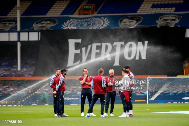 Aston Villa's English assistant manager John Terry , players and staff inspect the pitch prior to the English Premier League football match between...