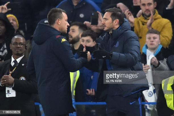 Aston Villa's English assistant manager John Terry shakes hands with Chelsea's English head coach Frank Lampard after the English Premier League...