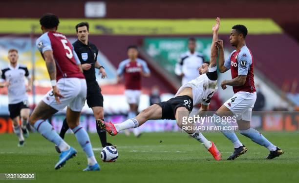 Aston Villa's English defender Ezri Konsa fouls Fulham's Serbian striker Aleksandar Mitrovic during the English Premier League football match between...