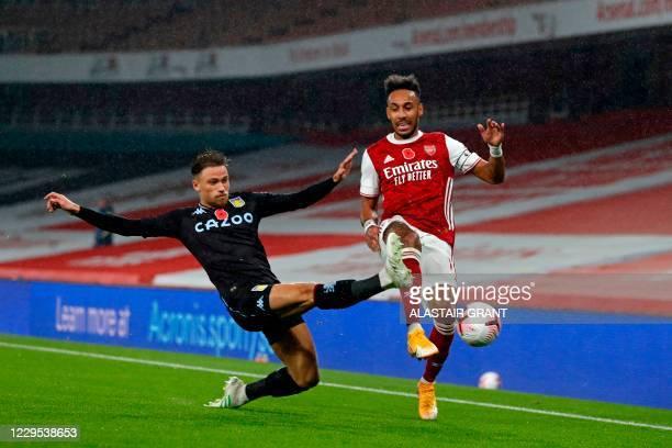 Aston Villa's English defender Matty Cash tackles Arsenal's Gabonese striker Pierre-Emerick Aubameyang during the English Premier League football...
