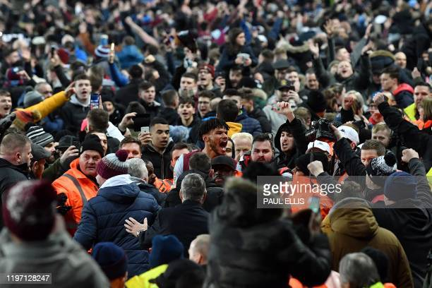 TOPSHOT Aston Villa's English defender Tyrone Mings is mobbed by fans during a pitch invasion after the English League Cup semifinal second leg...