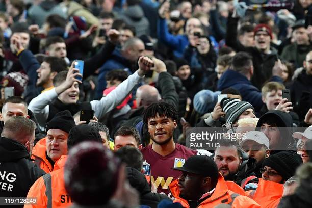 Aston Villa's English defender Tyrone Mings is mobbed by fans during a pitch invasion after the English League Cup semifinal second leg football...
