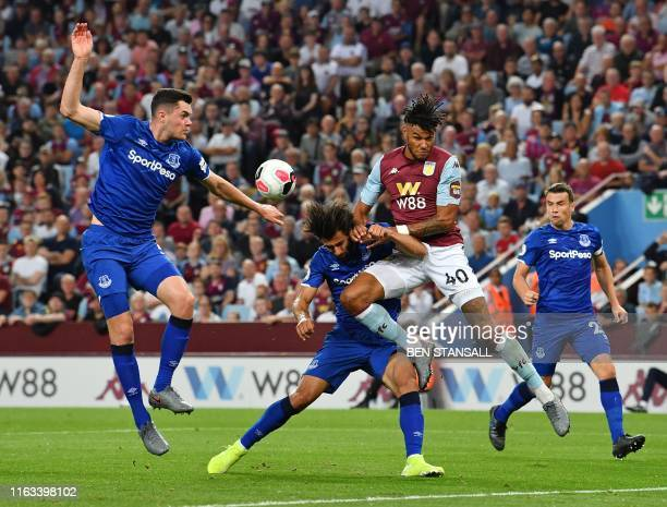 Aston Villa's English defender Tyrone Mings vies for the ball against Everton's Portuguese midfielder André Gomes and Everton's English defender...
