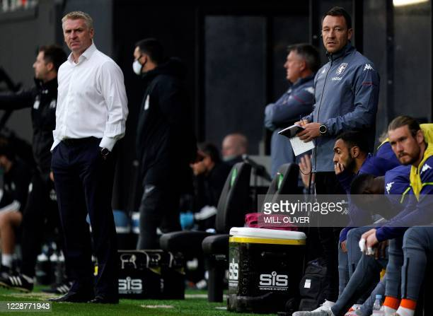 Aston Villa's English head coach Dean Smith and Aston Villa's English assistant coach John Terry watches his players from the touchline during the...
