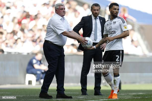 Aston Villa's English manager Steve Bruce hands the ball to Fulham's English defender Ryan Fredericks during the English Championship playoff final...