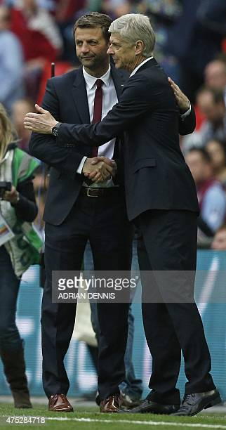 Aston Villa's English manager Tim Sherwood shakes hands with Arsenal's French manager Arsene Wenger follwing the FA Cup final football match between...